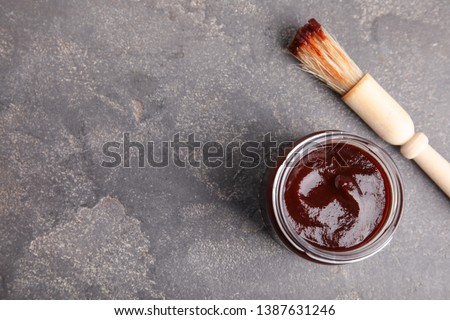 Jar with barbecue sauce and brush on grey background, flat lay. Space for text Сток-фото ©