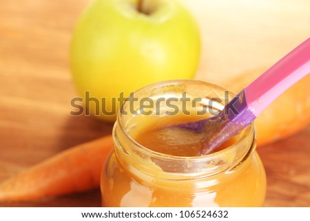 Jar with carrot and apple baby food, spoon and carrot and apple on wooden table close-up