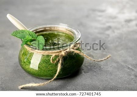Jar with chutney mint sauce on table