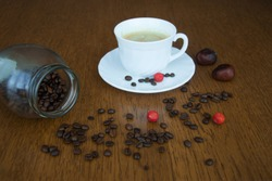 jar with coffee beans, a cup of coffee, chestnuts and berries on the table, autumn card