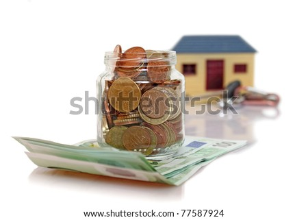 jar with coins in front of blurry house