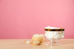Jar with cotton pads on wooden table against pink background. Space for text