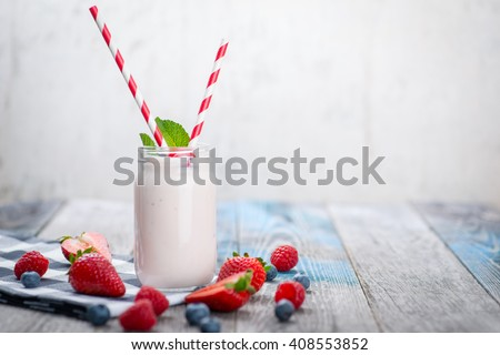 Jar with drinking yogurt, berries and straw on rustic wooden table