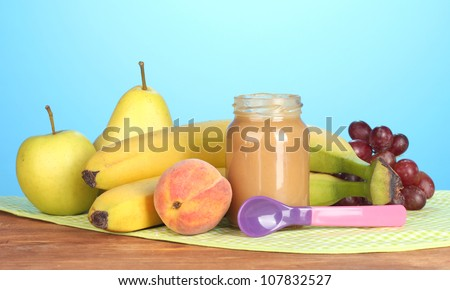 Jar with fruit baby food, spoon and fruits on colorful napkin on blue background