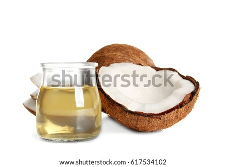 Jar with melted coconut oil and nut on white background