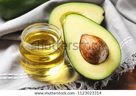 Jar with oil and ripe fresh avocado on table, closeup