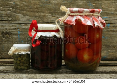 Jar with preserves. Homemade strawberry jam, pickled tomatoes and capers on wooden background. Series