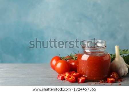 Jar with red chilli and tomato sauce, and spices on wooden table Stockfoto ©