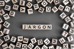 Jargon  - word from wooden blocks with letters,  special words and phrases jargon concept, random letters around, top view on grey background