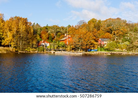 Jarnavik, Sweden - October 25, 2016: Environmental documentary of coastal lifestyle. Seaside homes with private piers in fall. Colorful woodland in background. #507286759