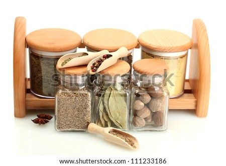 jars and wooden spoons on shelf with spices isolated on white