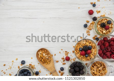 Jars full with granola and fresh berries and wood spoon full whit granola on white wood table, background ,top view, copy space #1121302850