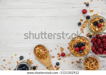 Jars full with granola and fresh berries and wood spoon full whit granola on white wood table, background ,top view, copy space #1121302922