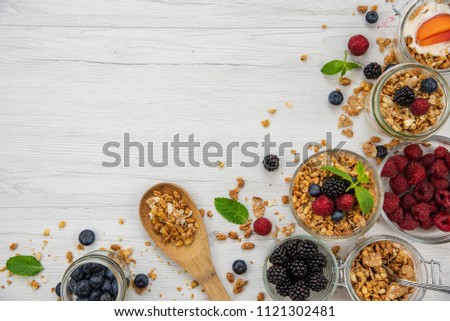 Jars full with granola, yogurt and fresh berries and wood spoon full whit granola on white wood table, background ,top view, copy space #1121302481