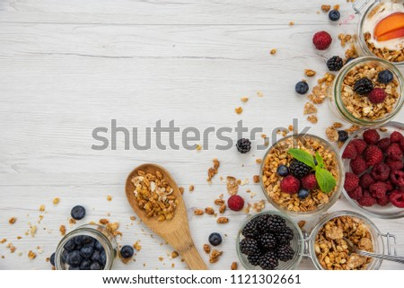Jars full with granola, yogurt and fresh berries and wood spoon full whit granola on white wood table, background ,top view, copy space #1121302661