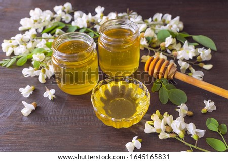 Photo of  jars of clear fresh acacia honey, honey stick and acacia flowers on the table close-up. background with fresh acacia honey in glass jars.