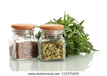 Jars of coriander seeds and green cardamom isolated on white close-up
