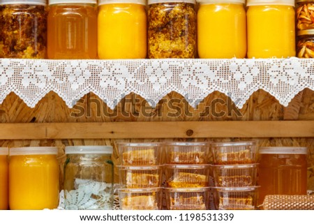Jars of different honey varieties on a shelf #1198531339