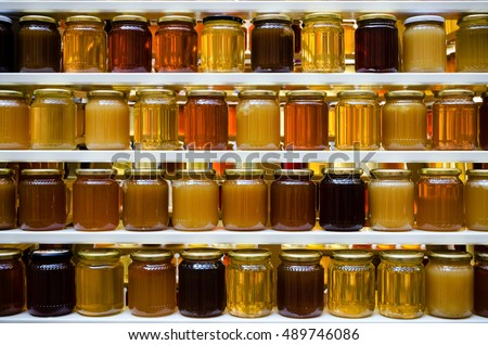 Jars of different honey varieties stocked on a shelf