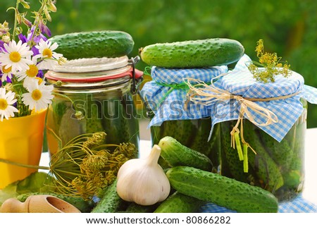jars of homemade preserves with pickled cucumbers on the table in the garden