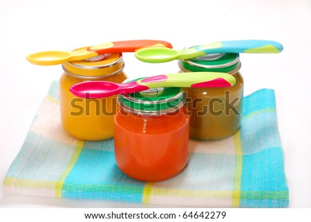 jars of various baby food and spoons isolated on white