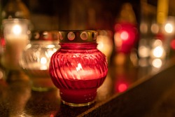 Jars with burning candles on stone surface at night