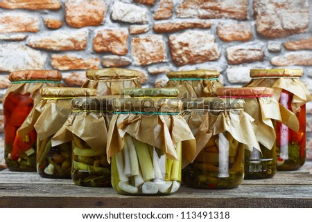 Jars with pickled vegetables arranged in order of bowling pins on wooden shelf against stone wall