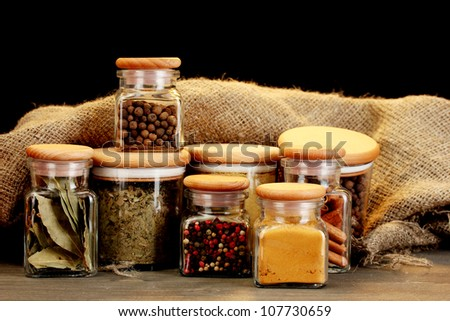 jars with spices on wooden table on black background - stock photo