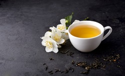 Jasmine flowers and cup of healthy tea  on a black background. Herbal medicine