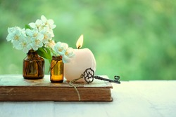 jasmine flowers, vintage key, candle, old book. spring or summer image. romantic spa relax still life. copy space
