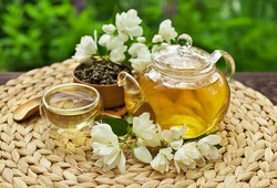 Jasmine green tea in a glass teapot with a glass cup and fresh blossoms