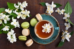 Jasmine green tea with sweet french macarons, dark wooden table. Top view