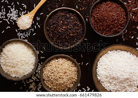 Jasmine rice, Brown rice, Red rice,Black rice, Mixed rice and Riceberry on rustic table, top view #661479826