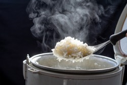 Jasmine rice cooking in electric rice cooker with steam on dark background. Soft Focus,