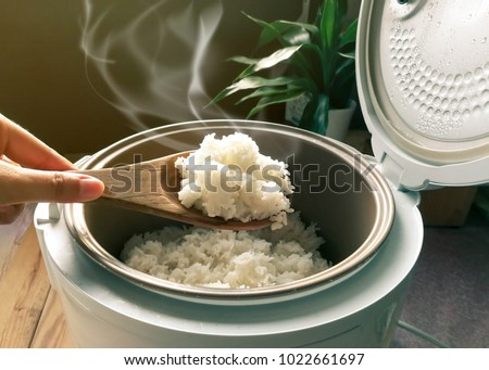 Jasmine rice cooking in electric rice cooker with steam. Soft Focus, Rustic tone picture. #1022661697