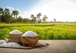 Jasmine steamed rice in wooden bowl with the chopsticks on the wooden table with the plantation rice at sunset
