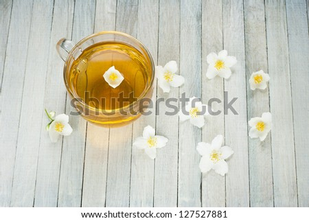 jasmine tea and jasmine flowers on white wooden background, top view
