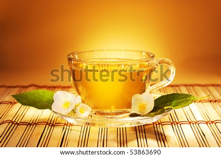 jasmine tea in soft warm evening light with fresh jasmine leaves and flowers