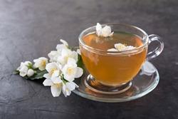Jasmine tea with jasmine flowers on a dark  background