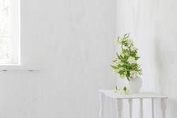 jasmineflowers in vase on background old wall