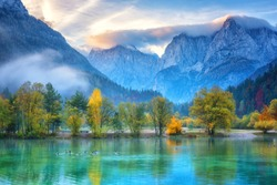 Jasna lake in Triglav national park at sunrise, Kranjska Gora, Slovenia. Amazing autumn landscape with Alps mountains, trees, blue sky with clouds and reflection in water, famous tourist attraction