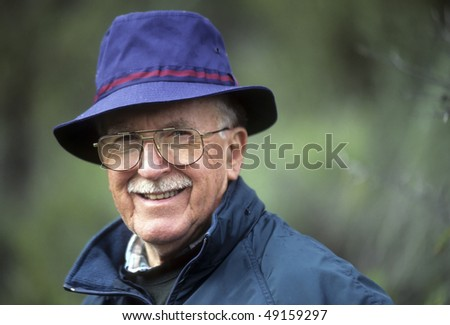 Jaunty dapper active senior man with hat, glasses, mustache, handsome, smiling.