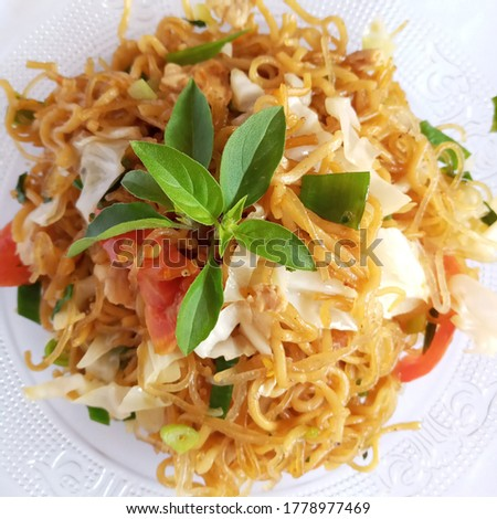 Javanese fried noodles, home-cooked noodles mixed with sautéed garlic, pepper, ebi, cabbage, leeks, celery, tomatoes with basil leaves topping ... it was very delicious Photo stock ©