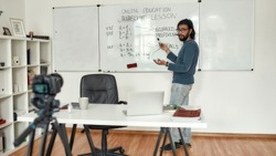 Javascript lesson. Young bearded male teacher wearing glasses pointing at whiteboard and teaching Javascript, giving lesson online. Recording video blog. Focus on a man. E-learning. Distance education