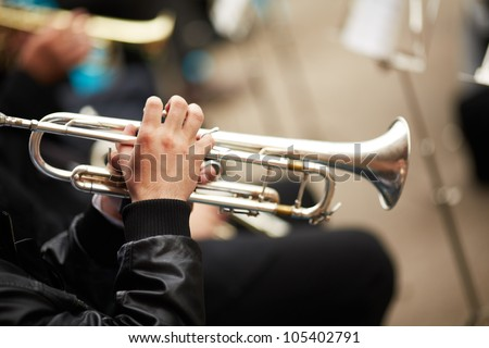 jazz band playing on the street, selective focus on the hands with trumpet