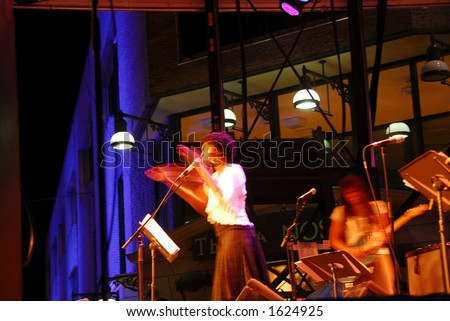 Jazz singer on outdoor stage clapping hands, blurred by long exposure
