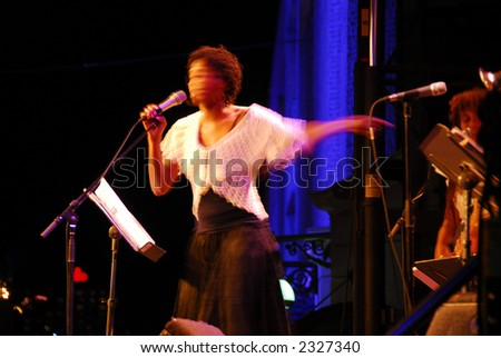 Jazz singer on outdoor stage, image is blurred by long exposure