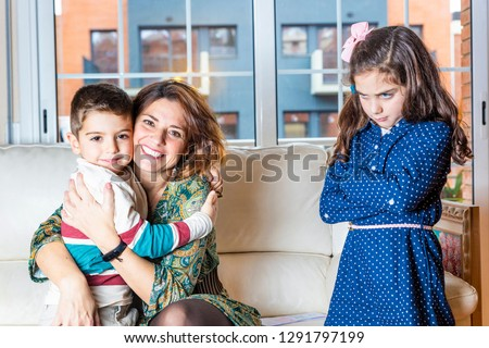 Jealous girl to see her brother hug her mother Stock photo ©