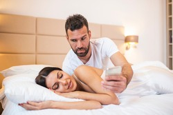 Jealous husband spying the phone of his partner while she is sleeping in a bed at home. Shocked jealous husband spying the phone of his wife while she sleeping in bed at home
