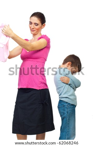 Jealous kid standing with arms folded and looking down while his mother admire a new baby clothes isolated on white background